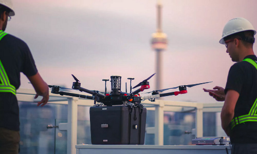 Workers with the lung-delivery drone on a hospital rooftop.